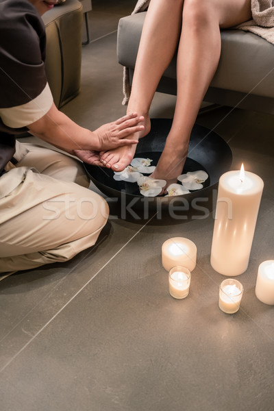 Hands of an Asian therapist during foot washing treatment Stock photo © Kzenon