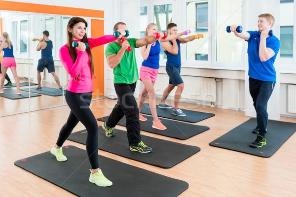 Group of athletes in gym doing gymnastics with dumbbells  Stock photo © Kzenon