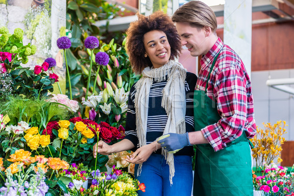 Beautiful woman buying freesias at the advice of a helpful vendor Stock photo © Kzenon