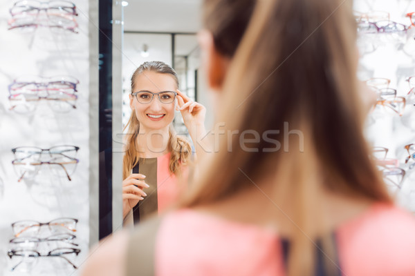 Young woman trying fashionable glasses in optometrist store Stock photo © Kzenon