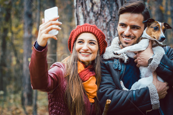 Woman and man with their dog on autumn walk taking a phone selfie Stock photo © Kzenon