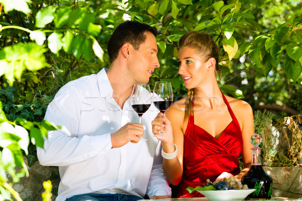 Woman and man sitting under grapevine and drinking Stock photo © Kzenon