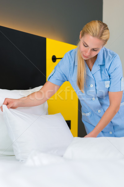 Stock photo: Service in hotel, maid puts clean sheets on bed