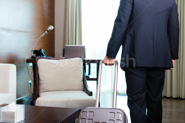 Manager in suit moving into hotel room with his suitcase Stock photo © Kzenon