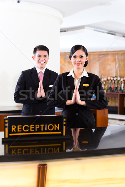 Chinese Asian reception team at hotel front desk Stock photo © Kzenon