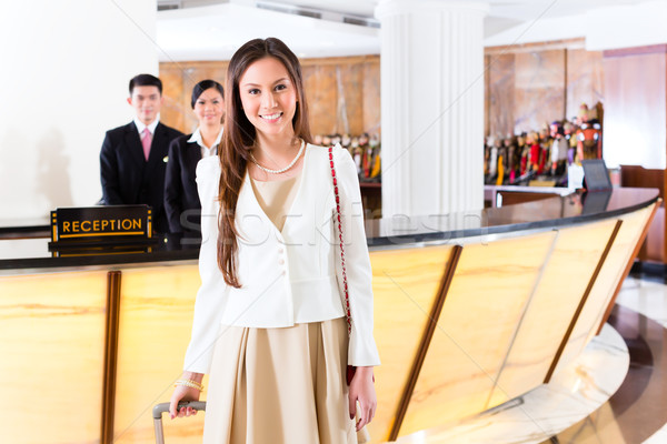 Asian Chinese woman arriving at hotel front desk Stock photo © Kzenon