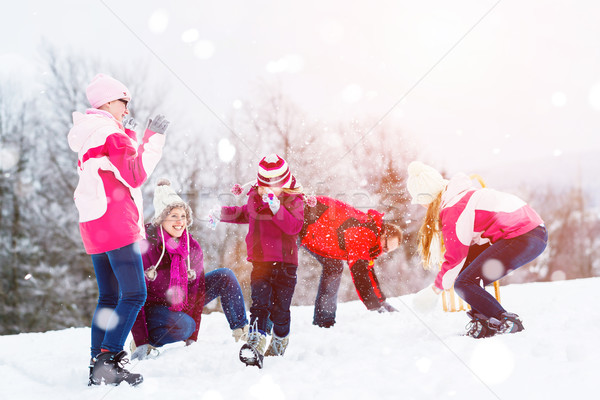 Family playing in snow having fight with snowballs Stock photo © Kzenon