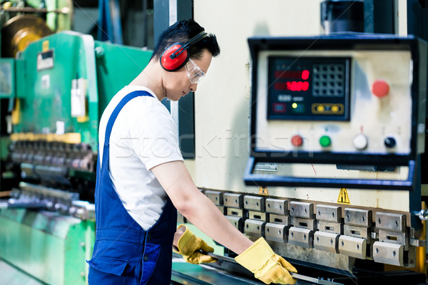 Asian machine operator in production plant Stock photo © Kzenon