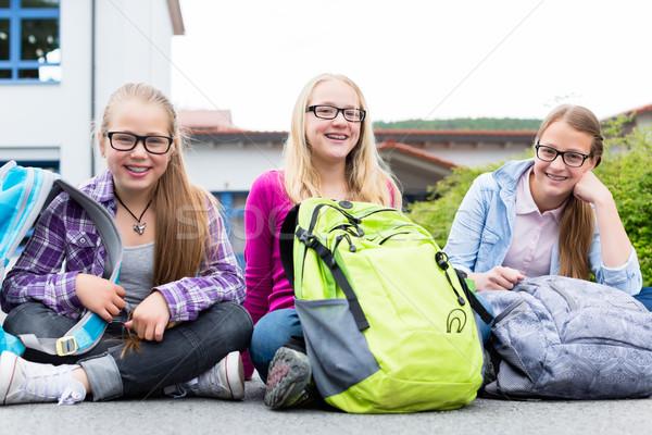 Schoolgirls sitting in schoolyard at school Stock photo © Kzenon
