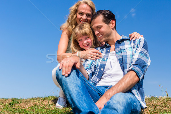 Girl on dads lap, Mom sitting next to them in field Stock photo © Kzenon