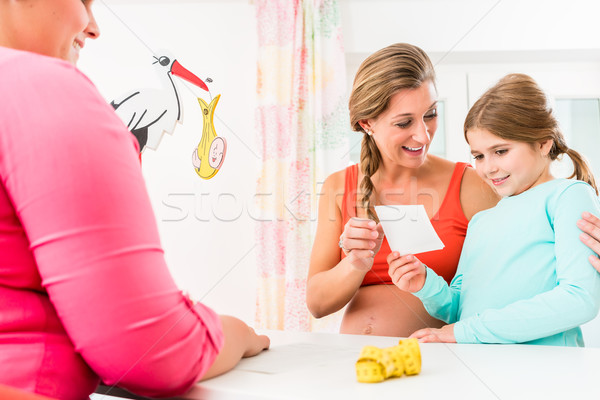 Expectant mother with sub-teenage daughter in her arm proudly pr Stock photo © Kzenon