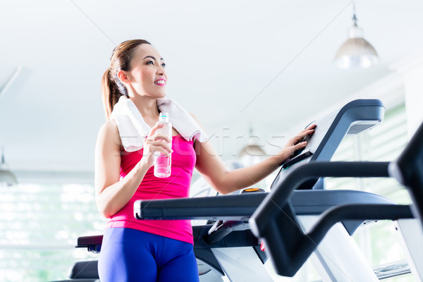Smiling woman on treadmill presenting water bottle Stock photo © Kzenon