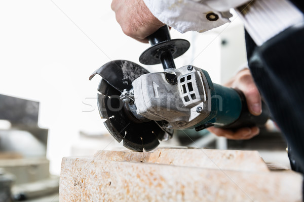 Handyman working at marble stone with disc grinder Stock photo © Kzenon