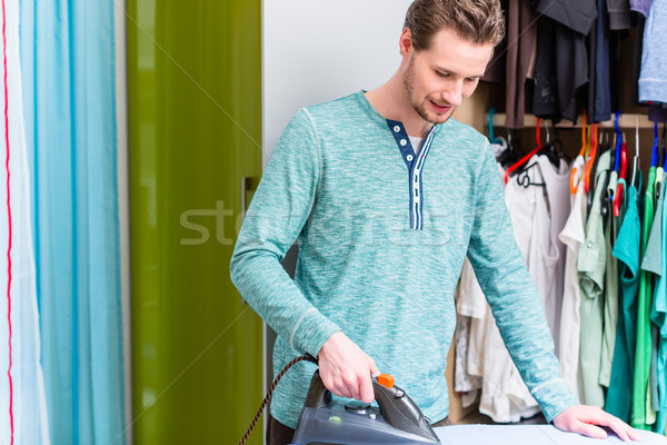 Man in front of wardrobe ironing the laundry Stock photo © Kzenon