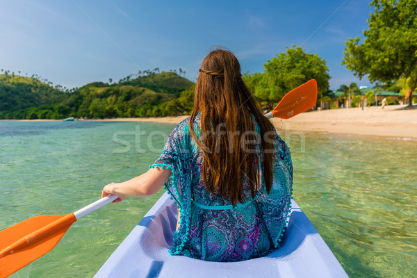 Young woman paddling a canoe along the shore of an idyllic islan Stock photo © Kzenon