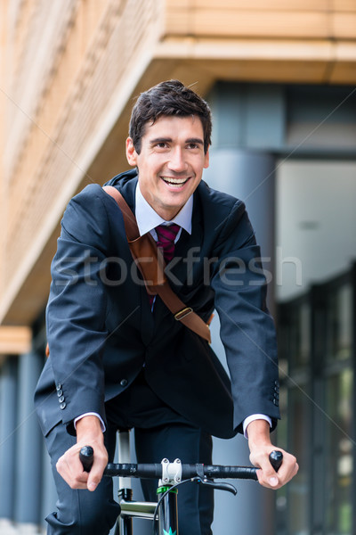 Active young man smiling while riding utility bicycle to his wor Stock photo © Kzenon