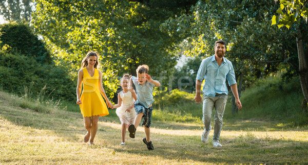 Active young parents with a healthy lifestyle running together w Stock photo © Kzenon