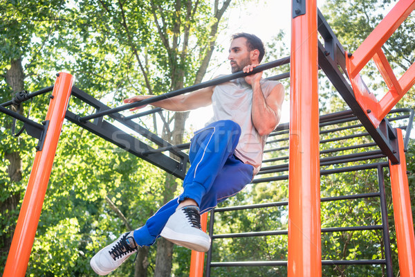 Strong young man doing amazing pull-up variation during extreme  Stock photo © Kzenon