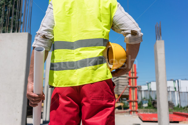 Midsection rear view of a worker holding a blueprint and a yellow hard hat Stock photo © Kzenon