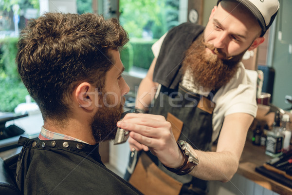 Handsome young man sitting on the chair of a barbershop Stock photo © Kzenon