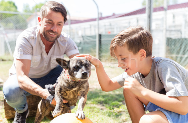 Dad and his son taking care of abandoned dog in animal shelter Stock photo © Kzenon