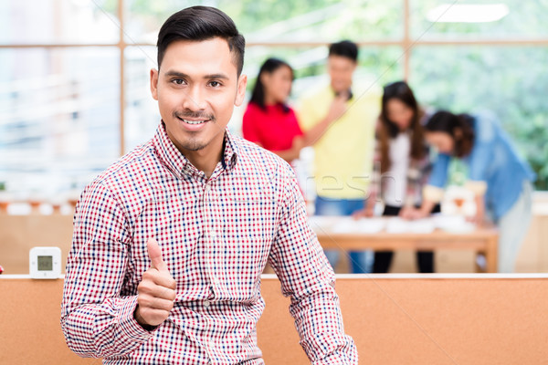 Portrait of young confident Asian employee showing thumb up  Stock photo © Kzenon