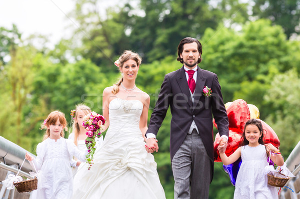 Stock photo: Wedding couple with flower children on bridge