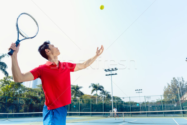 Chinese tennis player ready to hit the ball while serving Stock photo © Kzenon