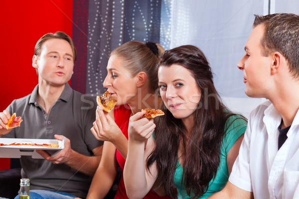 Friends eating pizza at home Stock photo © Kzenon