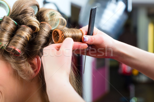 Woman at the hairdresser curling hair Stock photo © Kzenon