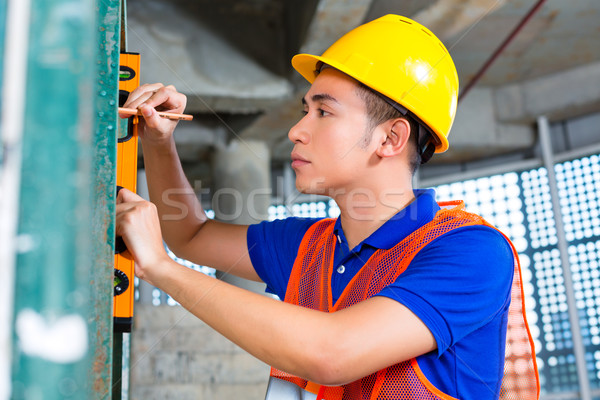 Builder or worker controlling building or construction site Stock photo © Kzenon
