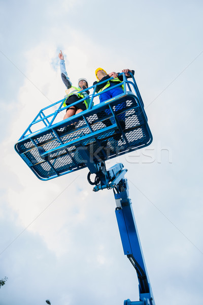 Construction workers on site in hydraulic lifting ramp Stock photo © Kzenon