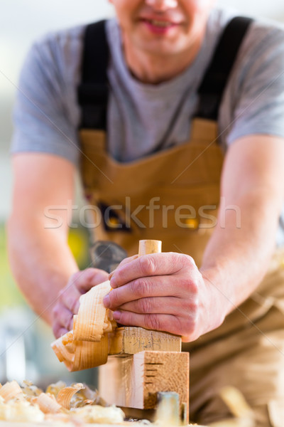 Carpenter with wood planer and workpiece in carpentry Stock photo © Kzenon