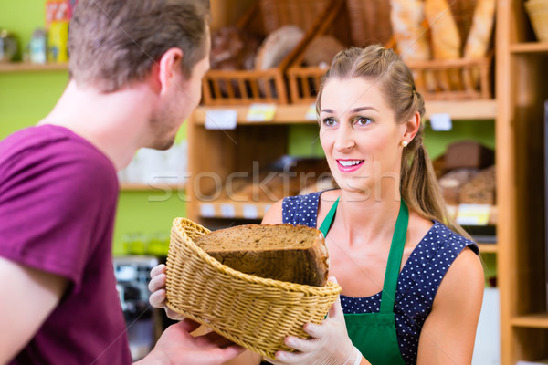 Bakery saleswoman offering bread  Stock photo © Kzenon