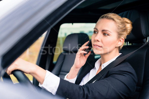 Woman using her phone while driving the car Stock photo © Kzenon