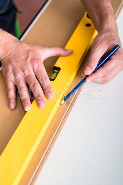 Workman with air level flooring home Stock photo © Kzenon