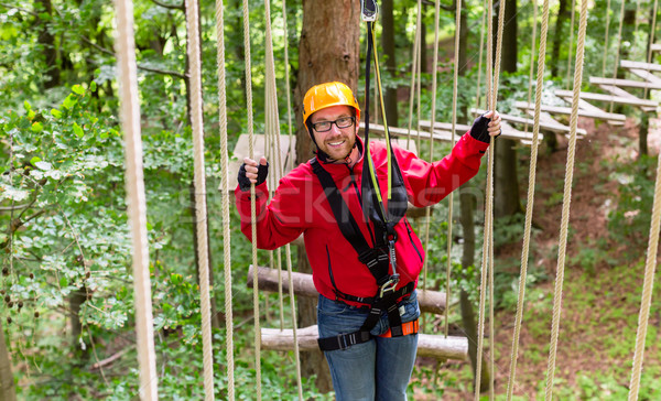 Man in high rope course climbing for sport Stock photo © Kzenon