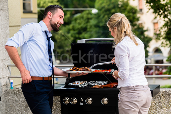Office colleagues grilling sausages at bbq after work Stock photo © Kzenon