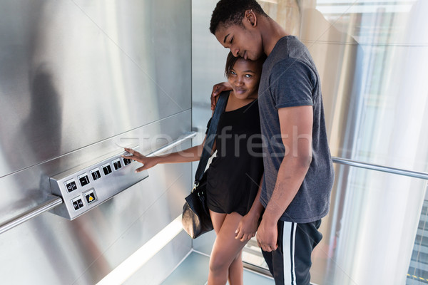 Affectionate young black couple standing in a modern elevator Stock photo © Kzenon