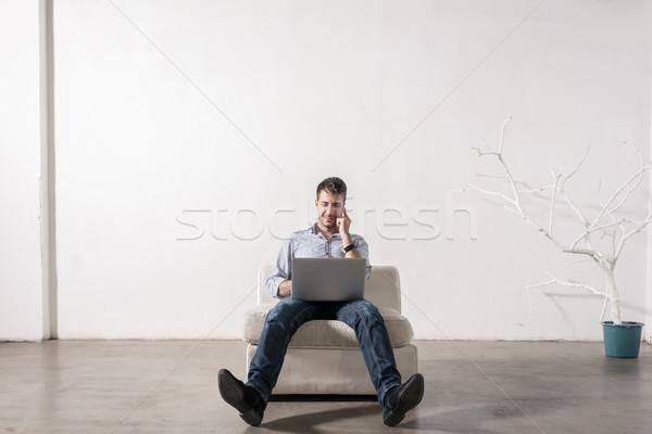 Jonge man vergadering lege kamer mobiele telefoon notebook pc Stockfoto © Kzenon