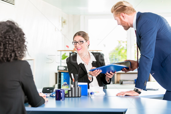 Man hands over a blue ring binder to his co-worker at the office Stock photo © Kzenon