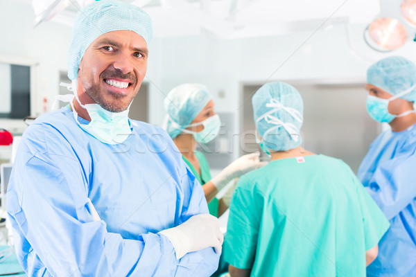 Hospital surgeons operating in operation room Stock photo © Kzenon