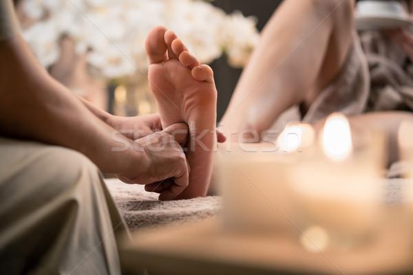 Woman having reflexology foot massage in wellness spa Stock photo © Kzenon