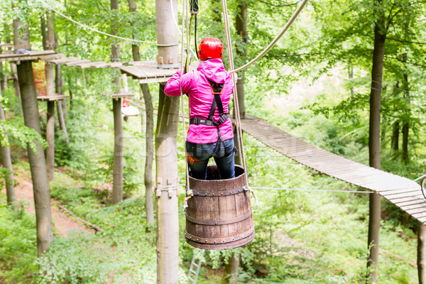 Woman sliding in barrel at high rope climbing course Stock photo © Kzenon