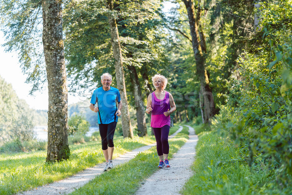 Two active seniors with a healthy lifestyle smiling while joggin Stock photo © Kzenon