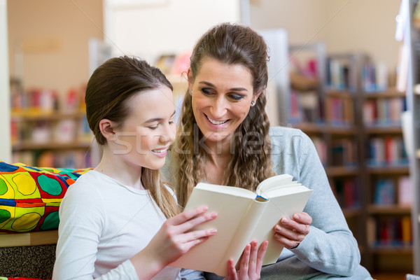 Mother and daughter reading a book in community center library Stock photo © Kzenon