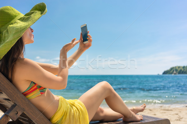 Young woman sending a love message through a selfie photo at the beach Stock photo © Kzenon