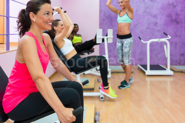 Woman in gym using modern equipment for toned arms Stock photo © Kzenon
