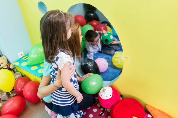 Caring teacher guiding a shy pre-school girl during playtime Stock photo © Kzenon