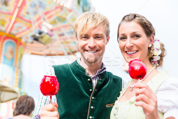 Couple in Bavarian clothes eating candy apples  Stock photo © Kzenon